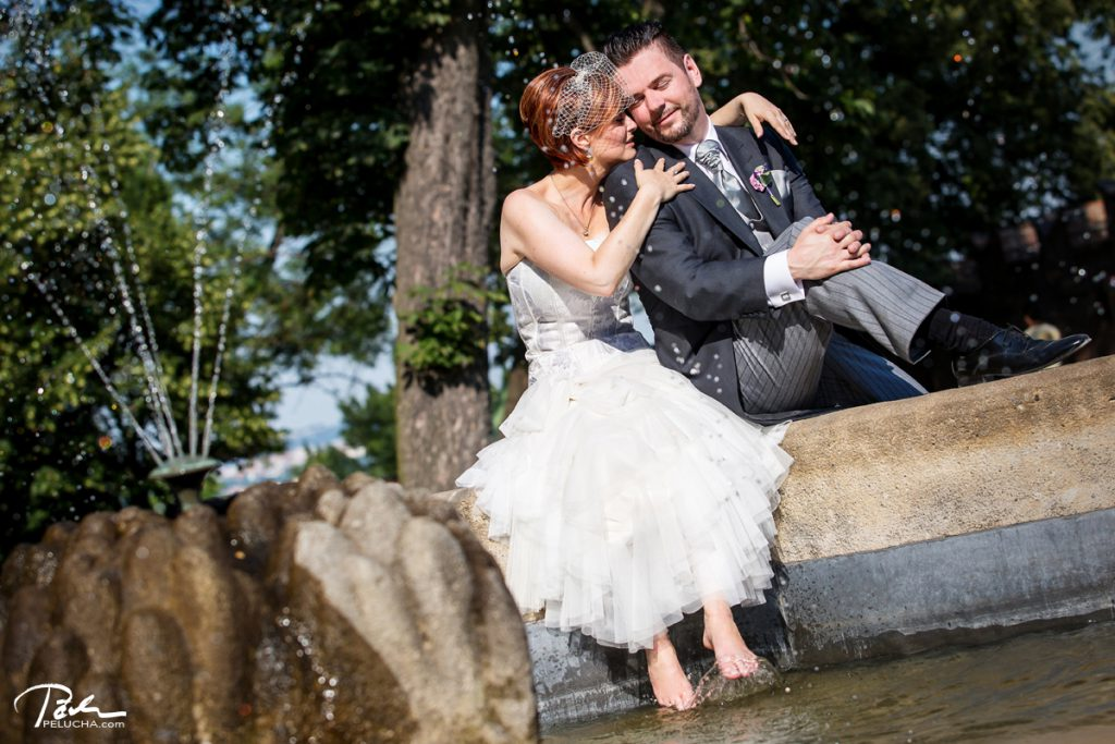 bride and groom sitting by the founting with her feet soaked in water