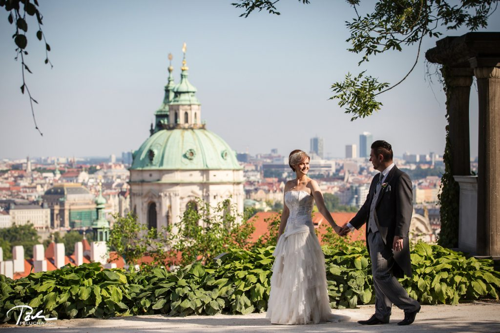 couple walking by hands with church in the background