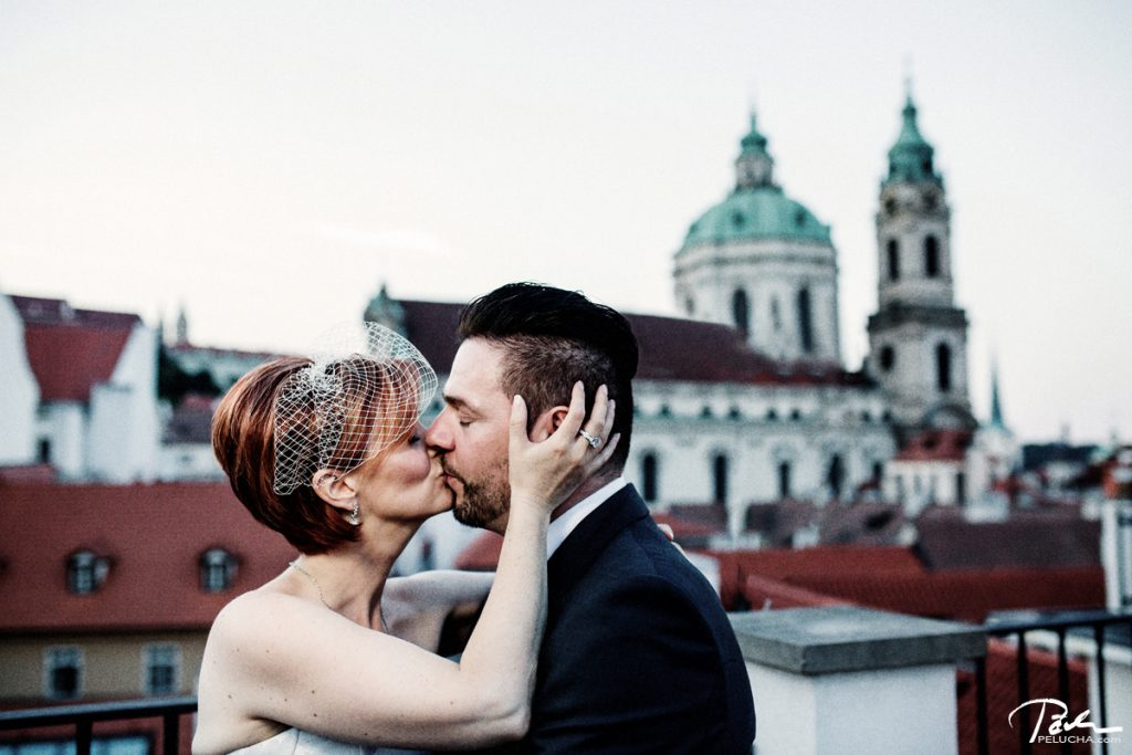 bride holding hands on her husband's face and kisssing him