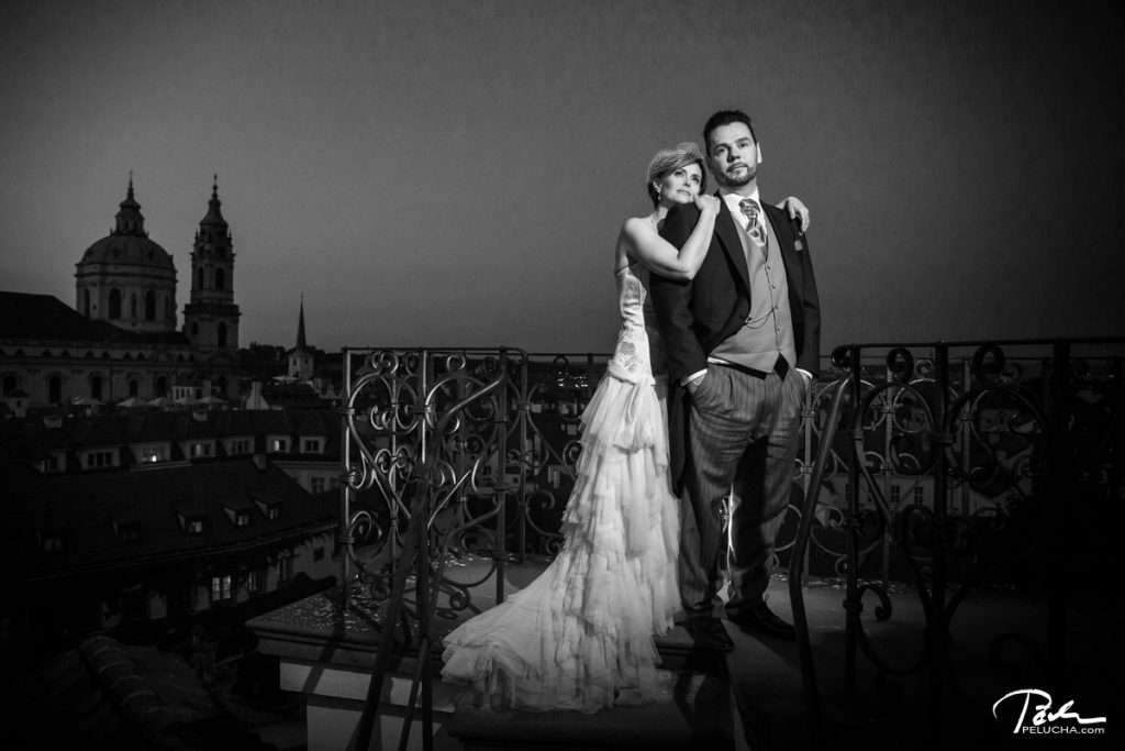 bride and groom standing on a terrace with a view over city in the background